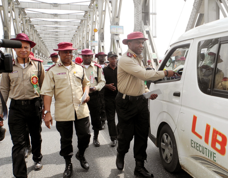 CORPS MARSHAL, FRSC, MR OSITA CHIDOKA (R), OFFICERS AND MEN OF THE CORPS, DISTRIBUTING LEAFLETS WITH ROAD SAFETY MESSAGES TO MOTORISTS ON THE RIVER NIGER BIDGE IN ONITSHA, ANAMBRA ON NEW YEAR'S DAY