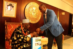 GOV. ROTIMI AMAECHI PRESENTING A SOUVENIR TO PRESIDENT OF THE SUPREME COUNCIL OF OGONI TRADITIONAL RULERS, KING GODWIN GININWA