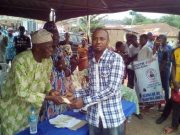 Engineer Adeleke Onasile hands over the cheque to Mr Abiodun Awobo at Hon Ladi Adebutu Award Event for SMEDAN Skills Acquisition Graduands in Remo North LG