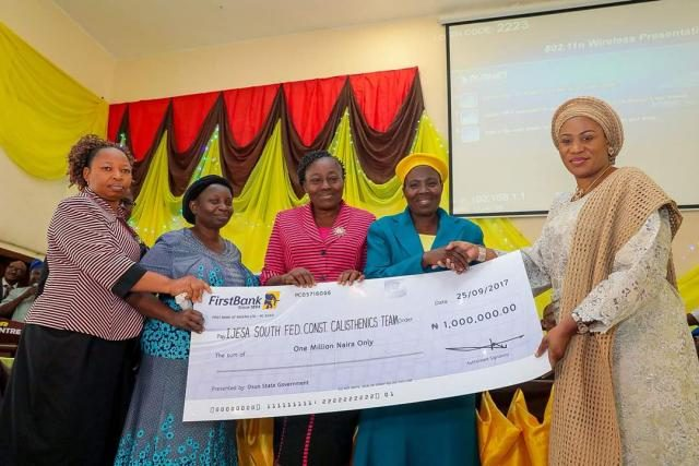 Wife of the Governor Rauf Aregbesola presenting N1m Cheque to the winners of the State of Osun Calisthenics Competitions which held in the 9 Federal Constituencies in the state.