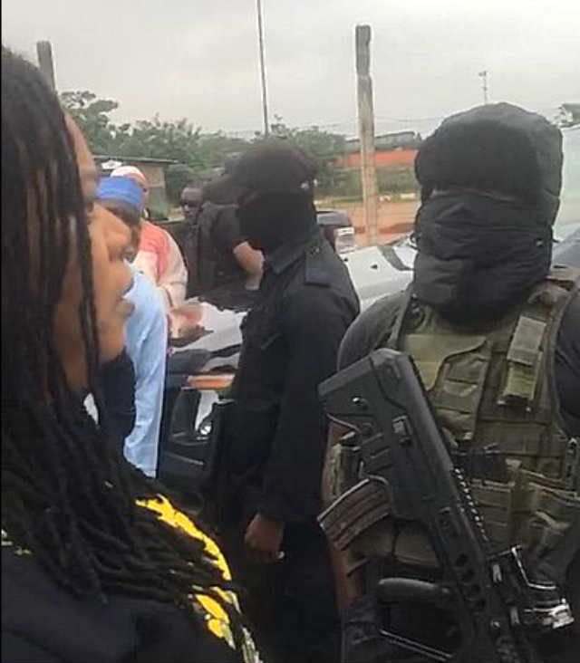 A woman in verbal engagement with masked security personnel at the NASS Complex, Abuja