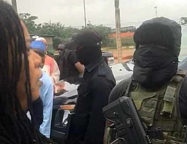 A woman in verbal engagement with masked security personnel at the NASS Complex Abuja