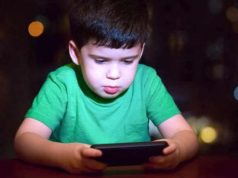 A Kid exploring his smartphone