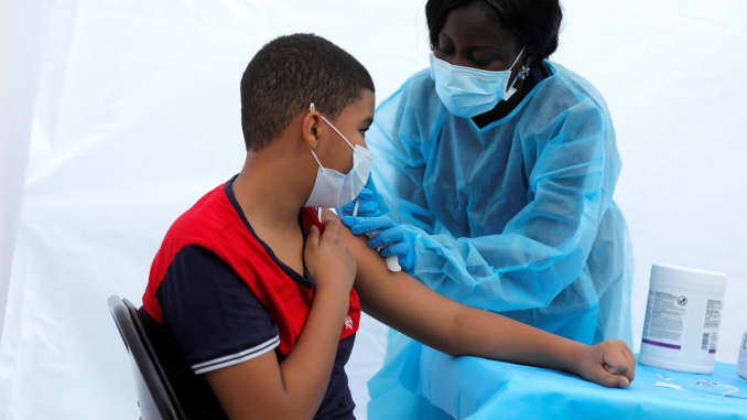 12-year-old Justing Concepcion receives a dose of the Pfizer-BioNTech vaccine for the coronavirus disease (COVID-19) from registered nurse Angela Nyarko, during a vaccination event for local adolescents and adults outside the Bronx Writing Academy school in the Bronx, New York City, June 4, 2021.