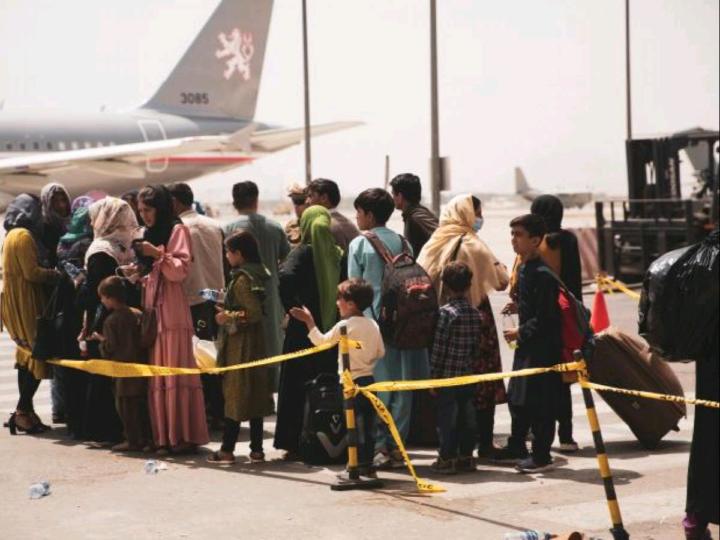 Civlians prepare to board a plane during an evacuation at Hamid Karzai International Airport, Kabul